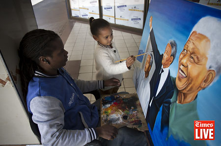 Five-year-old Zoe Harper is allowed to paint on a portrait by an artist by the signature of 'Emaz' of former South African president Nelson Mandela at the Rosebank Mall in Rosebank, Johannesburg. Nelson Mandela celebrates his 94th birthday on 18 July 2012. June 2012
