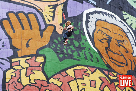 A lady swings in front of a mural of Nelson Mandela at the Orlando Cooling Towers during a bungee jump. Mar 2010