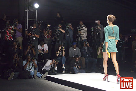 Photographers photograph a model as she walks down the catwalk during the Khosi Nkosi fashion show at the opening day of the Mercedes Benz Fashion Week Joburg, held in Newtown. March 2013
