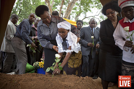 Mido Macia's wife, Biuda, breaks down as she plants a flower on the grave of her husband during his funeral service in Matola. March 2013