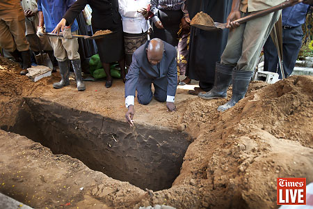 Mido Macia's father, Jossefa, scatters soil in the grave of his son. March 2013