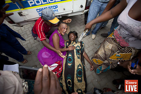 People protest outside the Benoni Magistrates court, east of Johannesburg, during the bail application of nine policemen accused of murdering a Mozambican national, Mido Macia, by dragging him behind a police vehicle last week. March 2013
