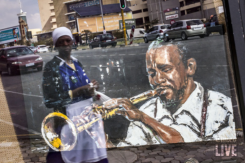 A woman is reflected in a window as she walks past a painting of American jazz trumpeter, Louis Armstrong, painted by contemporary artist, Berthold Moyo at the Soweto Fine Art Gallery in Hyde Park, Johannesburg. The gallery only showcases art originating from Soweto. May 2013