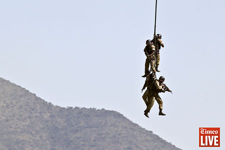 SANDF soldiers attached to a rope with their guns at the ready are airlifted during an air force capability demonstration. May 2013