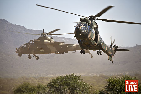 A South African Air Force Oryx helicopter flies past a Rooivalk helicopter. May 2013
