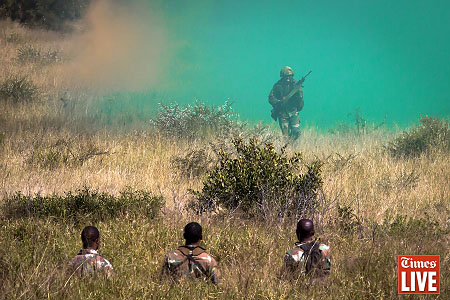 A SANDF soldier runs through green smoke. May 2013
